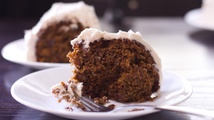applesauce bundt cake two slices on white plates one in front of the other with fork on front image