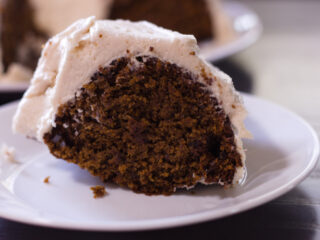 slice of dark cake with frosting on a white plate