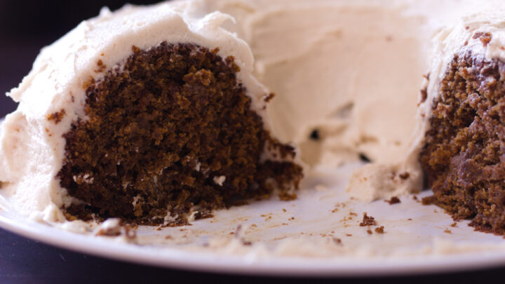 applesauce spice cake with slices cut from it on white plate