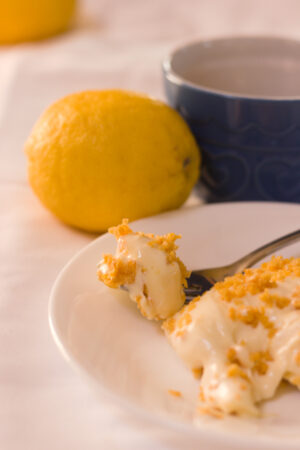 vertical image of lemon dessert portion and fork has uneaten bar on it with lemon and small blue dish