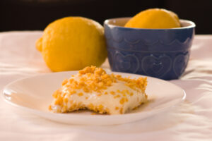 no bake lemon dessert on white plate with lemons