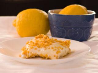 no bake lemon dessert on white plate with lemons