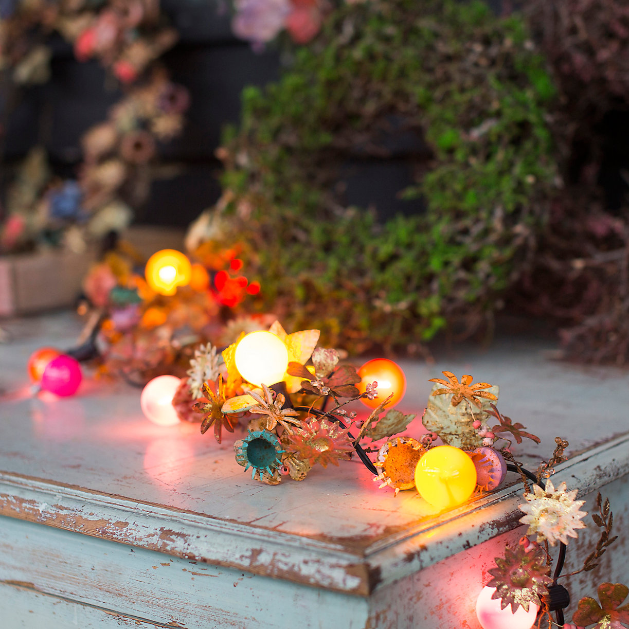 fairy light garland in pinks, yellows, blues on weathered blue dresser