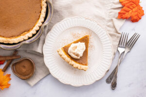 overhead shot of pumpkin pie with whipped cream on a white plate, white napkin two forks and pumpkin pie in the background