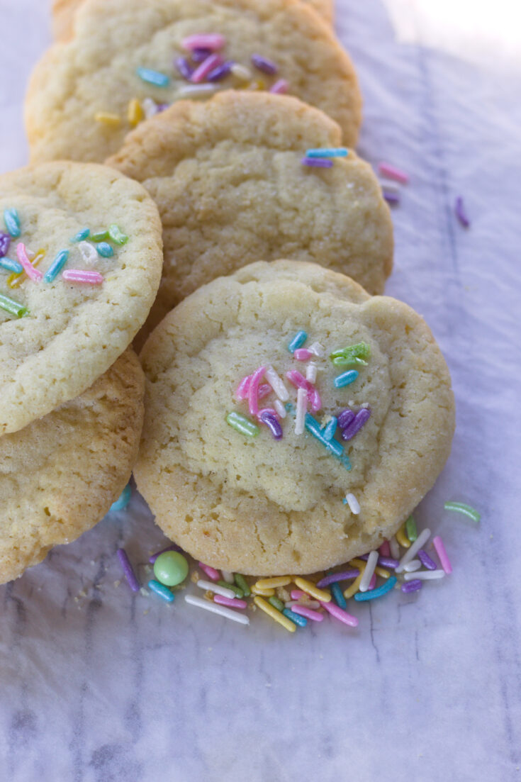 best soft and chewy sugar cookies stacked on top of each other on parchment paper