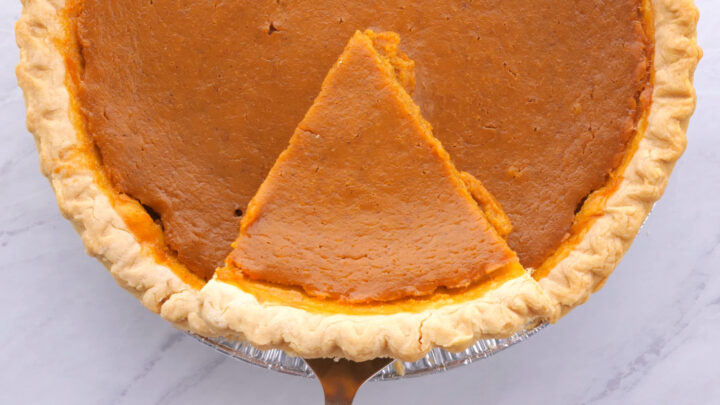 overhead view of pumpkin pie sliced with pie server under a piece of pie