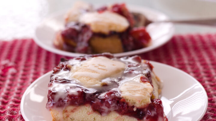 cherry dessert on white plate and red checked cloth