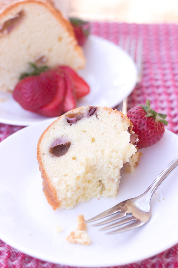 eating a slice of strawberry pound cake with cream cheese fork on white plate and second slice in background