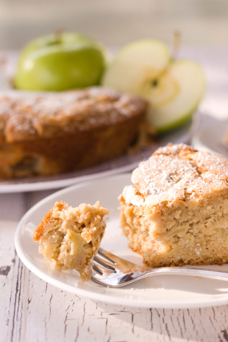 vertical image of partly eaten slice of french apple cake on white plate green apples and remainder of cake in background