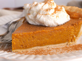 closeup view of pumpkin pie with whipped cream