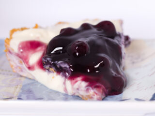 no bake blueberry cheesecake front view slice on blue plate