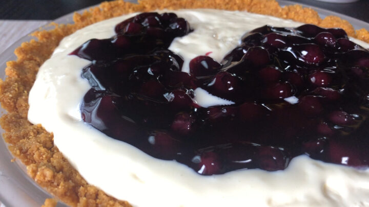 spooning on the blueberry pie filling on top of the blueberry cheesecake pie