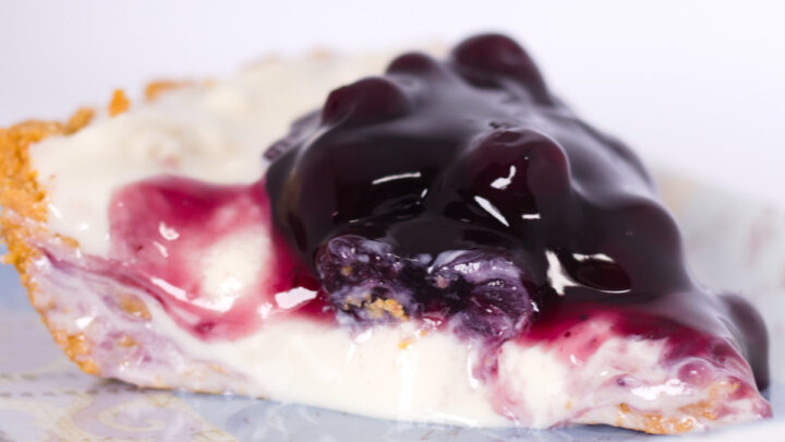 closeup view of no bake blueberry cheesecake pie on square blue plate