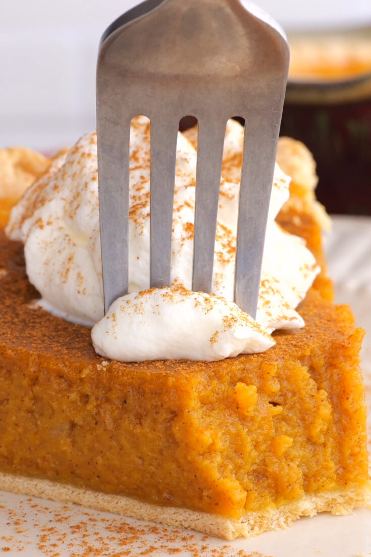 fork pushing into slice of pumpkin pie with whipped cream sprinkled with cinnamon