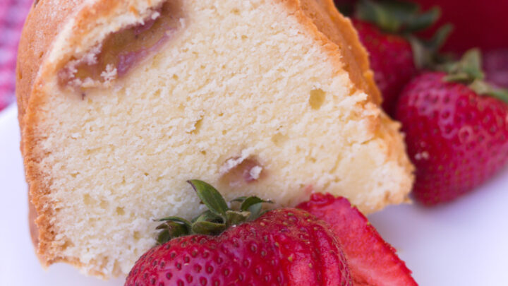 piece of strawberry pound cake on white plate with sliced strawberry square