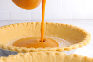 pouring pumpkin pie filling into pie shells