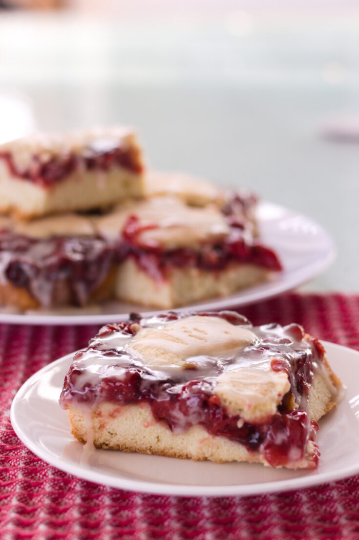 cherry pie bar on a white plate in front with blurred background