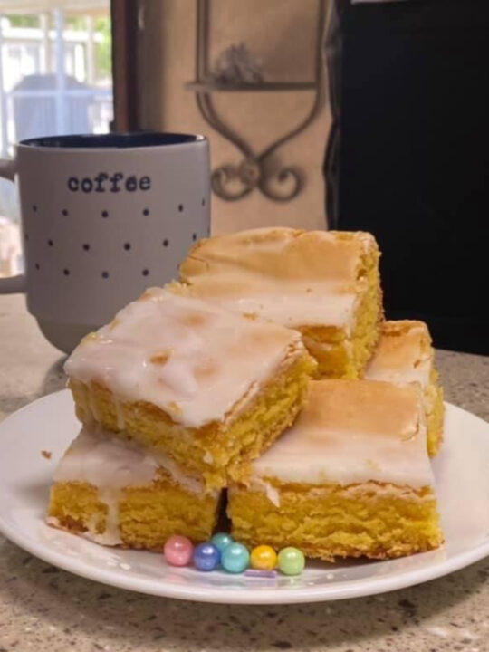 stack of lemon cake mix brownies on a white plate with pastel sprinkle beads and a mug of coffee in the background