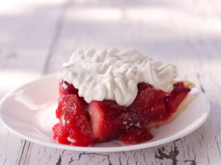 strawberry pie recipe with jello topped with whipped cream on white plate