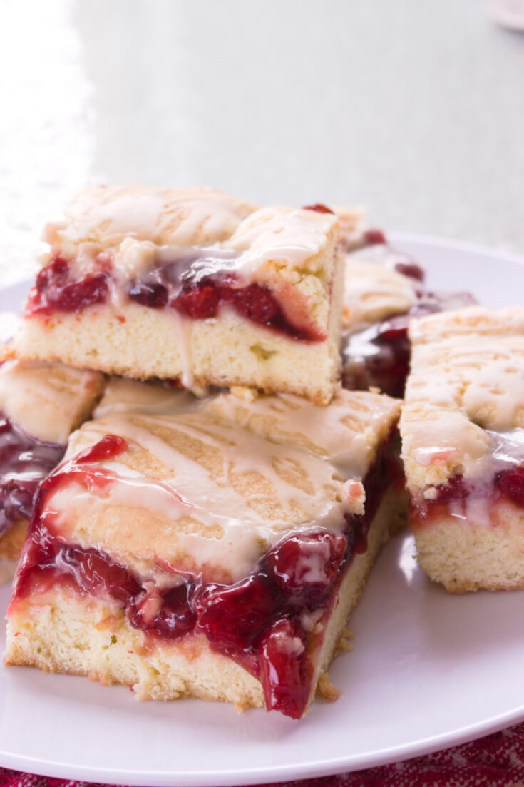 pile of cherry pie bars on a white plate