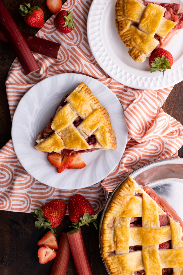 overhead image of strawberry rhubarb pie two servings and rest of pie in pie plate table decorations