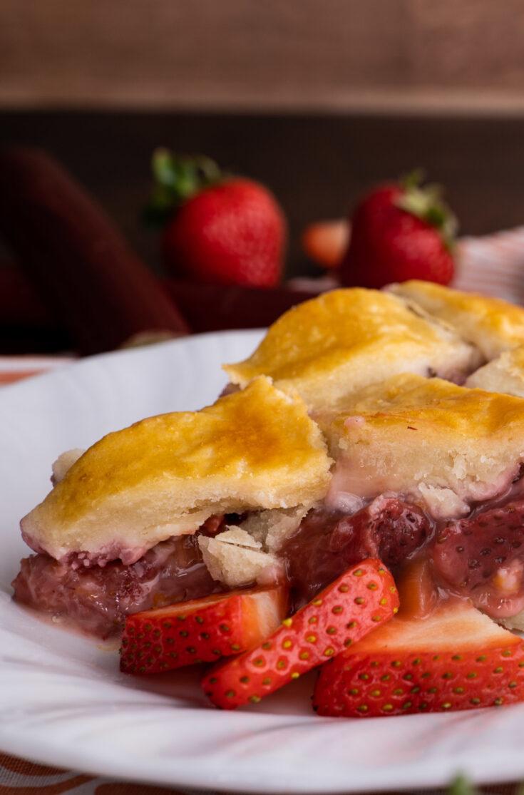 homemade strawberry rhubarb pie recipe closeup with sliced strawberries