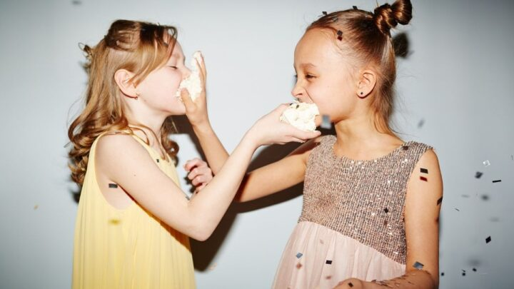 two little girls feeding each other cake one in yellow dress one in pink dress