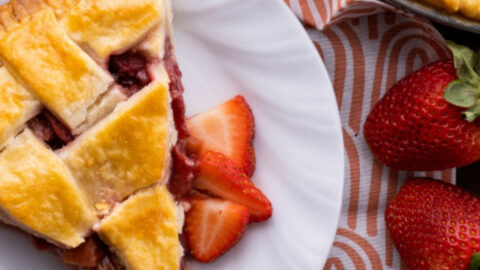 easy strawberry rhubarb pie on white plate overhead with fresh berries