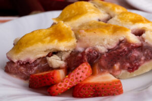strawberry rhubarb pie on white plate with berries