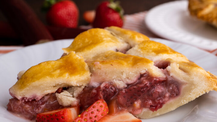 closeup view of strawberry rhubarb pie on white plate with sliced berries