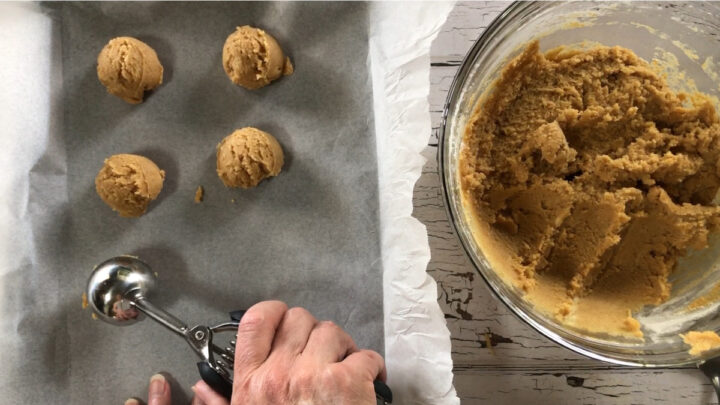 using cookie scoop to place balls of cookie dough on baking sheet