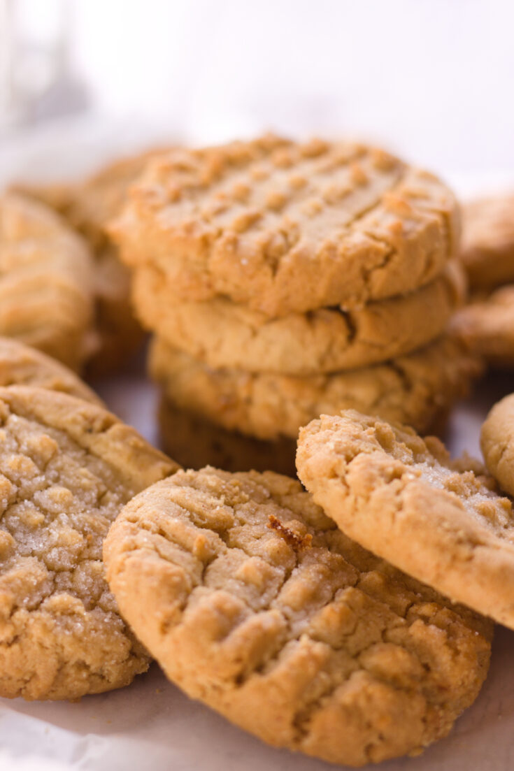 pile of soft peanut butter cookies on parchment paper