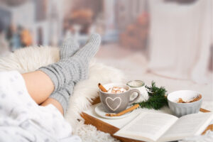 woman on bed with gray socks, cup of coffee with heart on it, cozy blankets and tray
