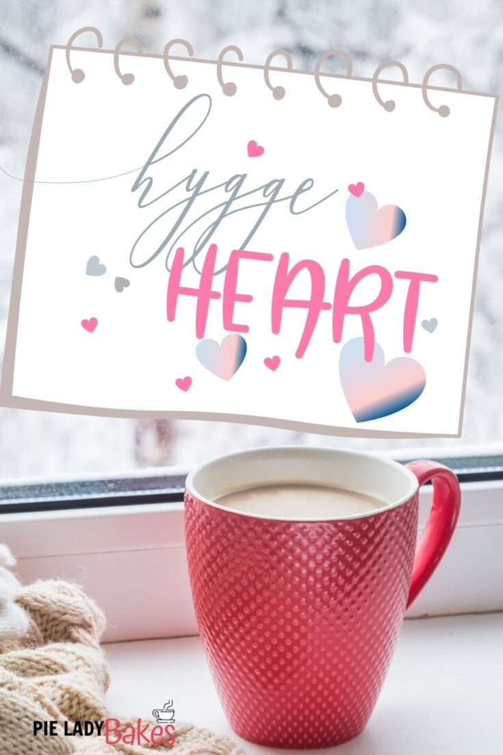 hygge heart design on a note card with a red mug of hot chocolate and blanket by window