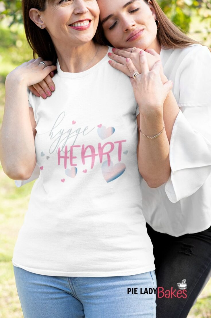 two woman hugging white t shirt says hygge heart
