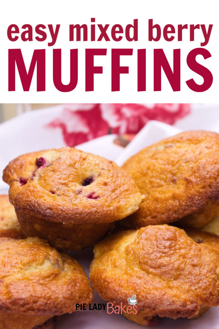 mixed berry muffins on a white plate with pink floral napkin in background pink text says easy mixed berry muffins